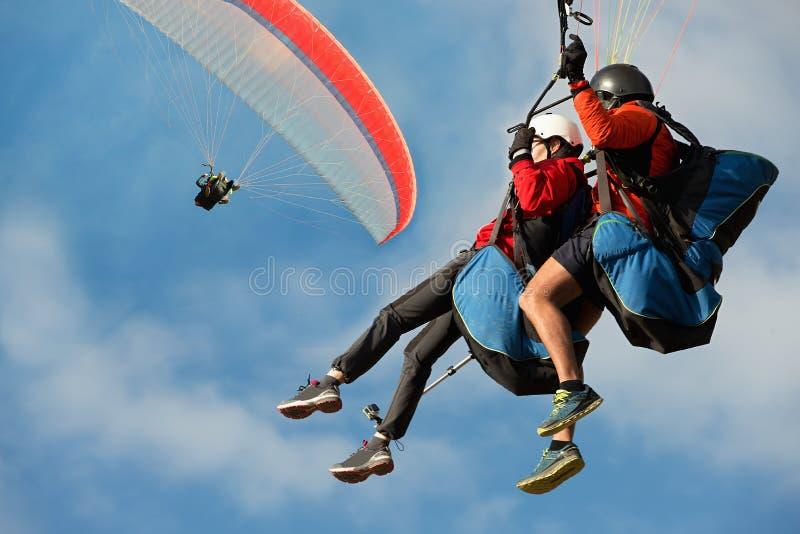 Mouche tandem de deux parapentistes contre le ciel bleu image stock