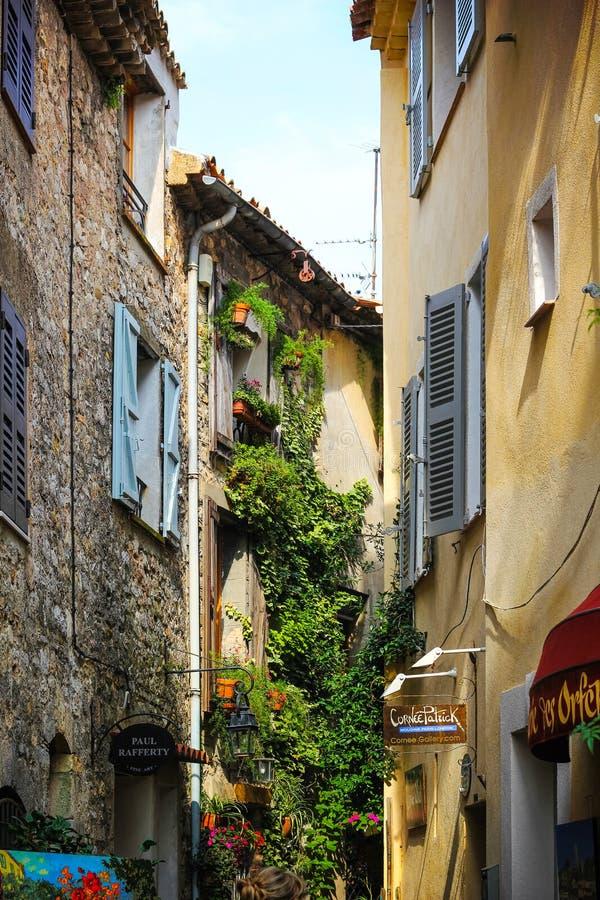 Mougins, Frankrijk - 6 augustus 2011: smalle straat door bakstenen huizen en een aantal typische provisiewinkels stock foto's