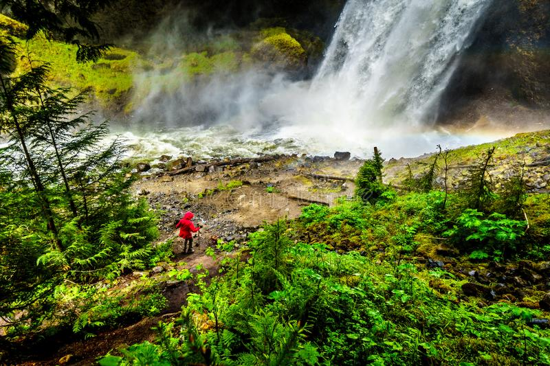 Moul Falls in Grouse Creek in Wells Gray Provincial Park at Clearwater, Briti. Woman in a Wind Breaker in the mist at the bottom of Moul Falls in Grouse Creek in royalty free stock images