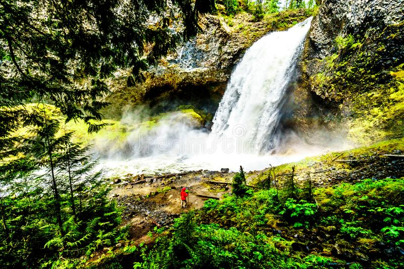Moul Falls in Grouse Creek in Wells Gray Provincial Park at Clearwater, Briti. Woman in a Wind Breaker in the mist at the bottom of Moul Falls in Grouse Creek in stock images