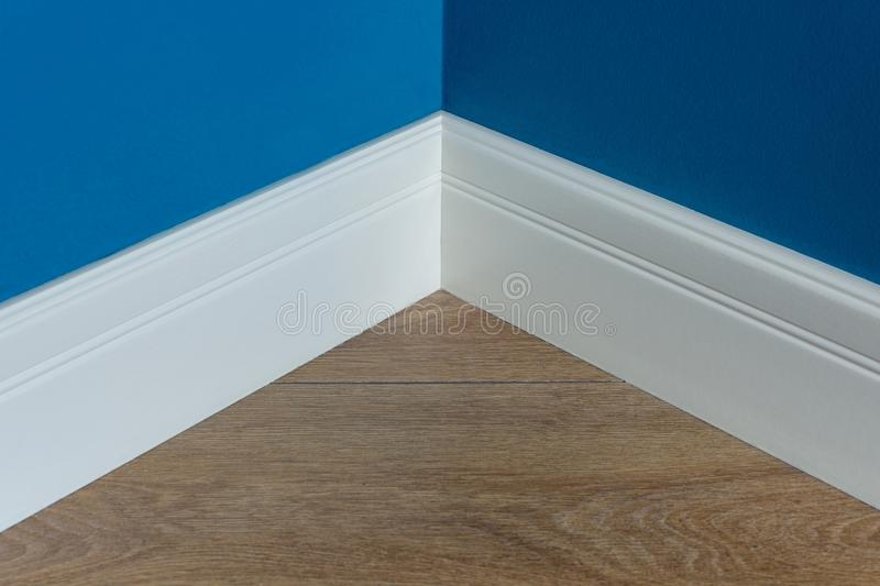 Moulding in the corner. Blue Matte Wall with laminate immitating oak texture.  royalty free stock image