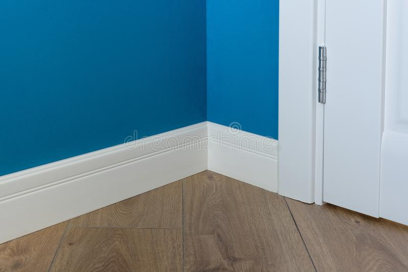 Moulding in the corner. Blue Matte Wall with laminated parquet floors immitating oak texture royalty free stock photo