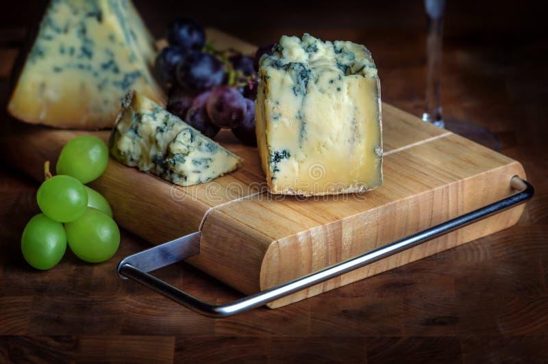 Mouldy azul maduro e uvas do stilton da placa do queijo foto de stock