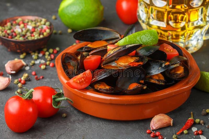Moules dans les coquilles avec les tomates et la sauce épicée images stock