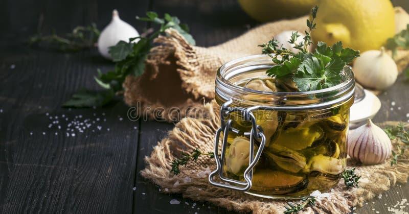 Moules en boîte en huile et jus de citron d'olive avec les épices, l'ail et les herbes, table de cuisine en bois noire, foyer sél photos libres de droits