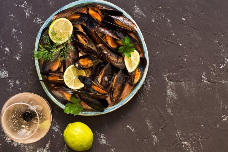 Moules en sauce au vin sur un fond concret noir, un verre de vin, chaux Vue supérieure, l'espace de copie mozzarella méditerranée photos stock