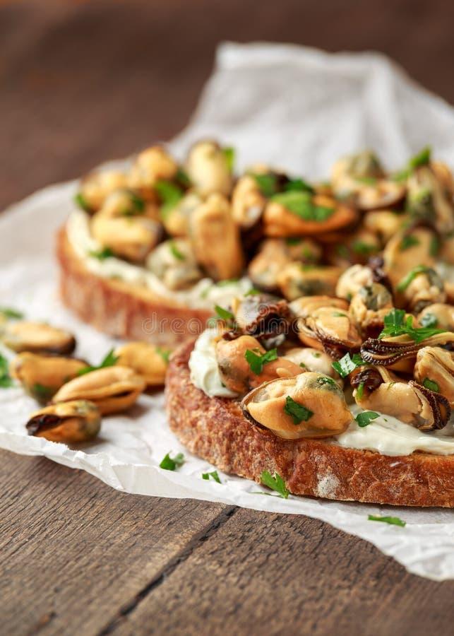 Moules faites maison sur la bruschette grill?e, le pain grill? avec le fromage ? p?te molle et les herbes photos libres de droits