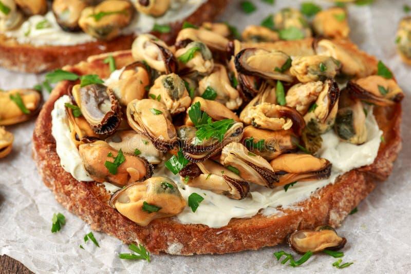 Moules faites maison sur la bruschette grill?e, le pain grill? avec le fromage ? p?te molle et les herbes images stock