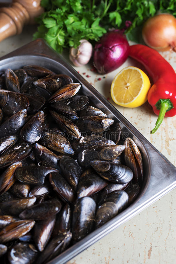 Moules fraîches avec des ingrédients pour faire cuire sur le fond rustique, vue supérieure, frontière Concept de fruits de mer image libre de droits