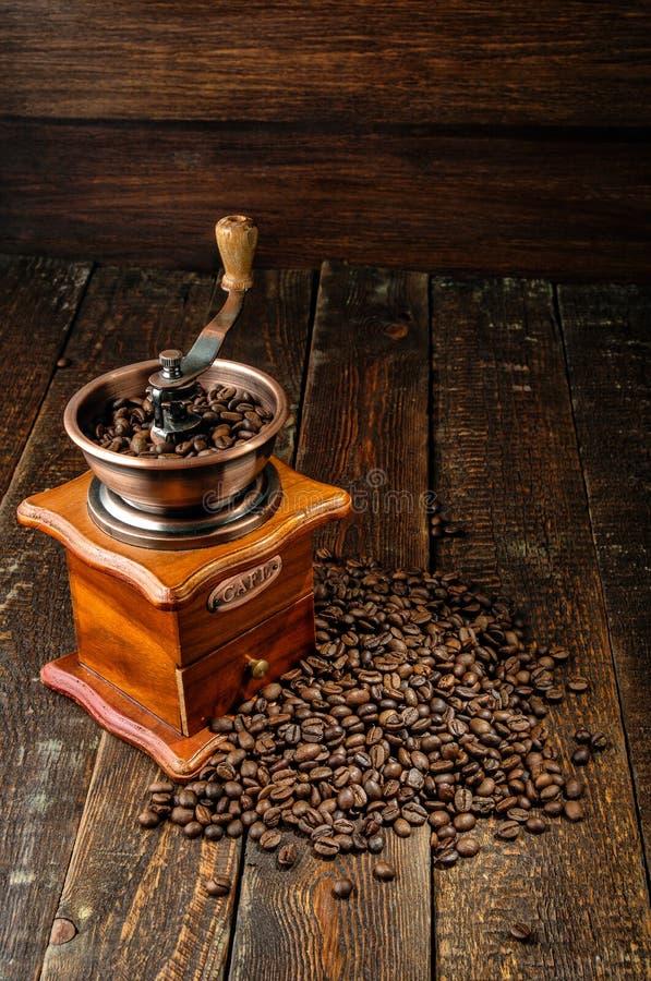 Moulin à café avec des grains de café sur la table en bois foncée photo stock