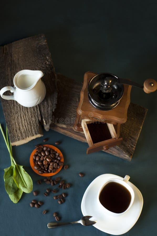 Moulin à café, tasse blanche de café, des grains de café et de la cruche de lait image stock