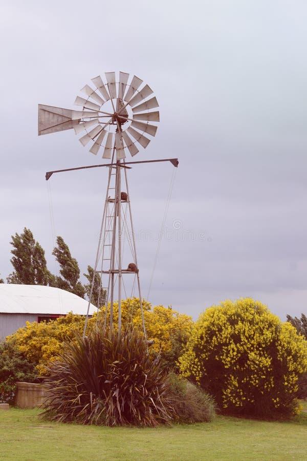 Moulin à vent antique à la ferme en condition de travail images stock