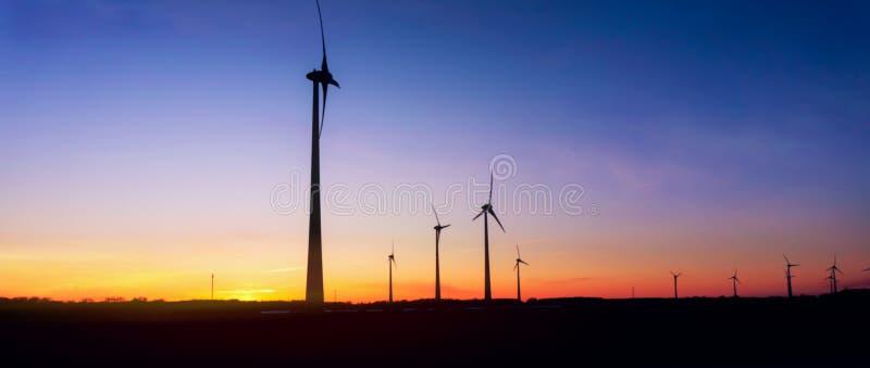 Moulin à vent au coucher du soleil Ferme de turbines de vent photo stock
