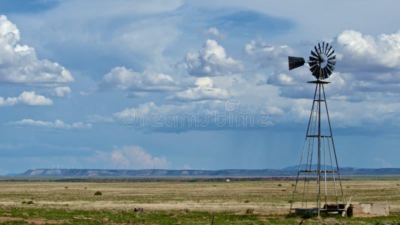 Moulin à vent avec une ferme de vent éloignée photographie stock libre de droits