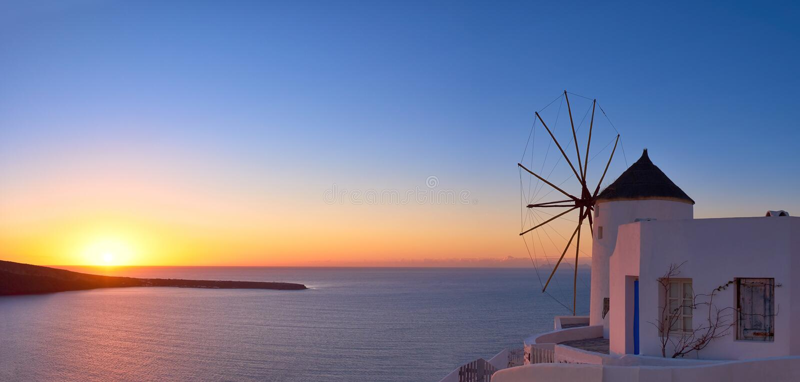 Moulin à vent dans le village d'Oia sur Santorini, Grèce, au coucher du soleil photographie stock libre de droits