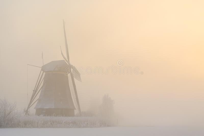 Moulin à vent dans un lever de soleil brumeux d'hiver photographie stock libre de droits