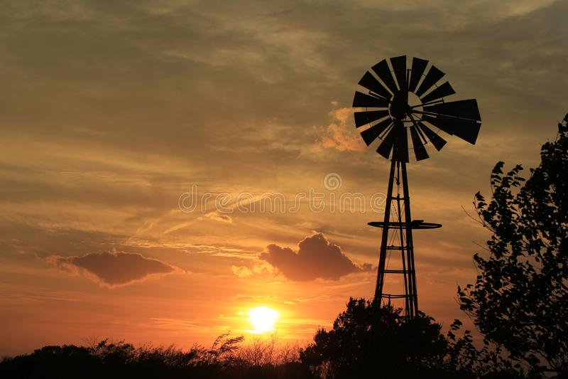 Moulin à vent de coucher du soleil du Kansas avec le ciel gris et les nuages blancs images libres de droits