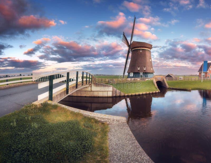 Moulin à vent et pont près du canal de l'eau au lever de soleil photographie stock