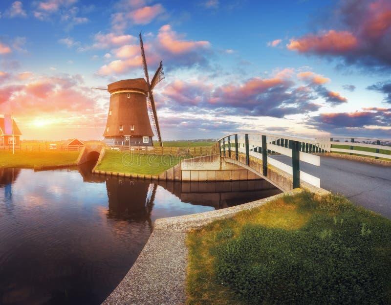 Moulin à vent et pont près du canal de l'eau au lever de soleil photos stock