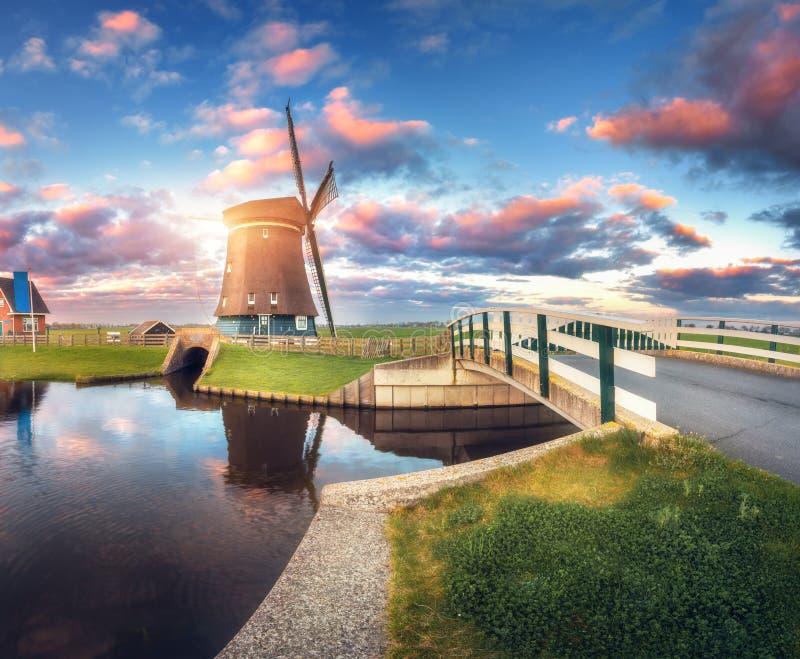 Moulin à vent et pont près du canal de l'eau au lever de soleil photos libres de droits