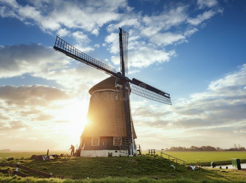 Moulin à vent et silhouette d'un homme au lever de soleil aux Pays-Bas photo stock