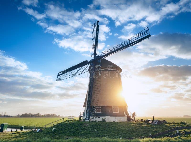 Moulin à vent et silhouette d'un homme au lever de soleil aux Pays-Bas photo libre de droits