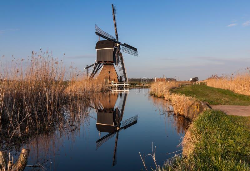 Moulin à vent néerlandais reflété en rivière photo stock