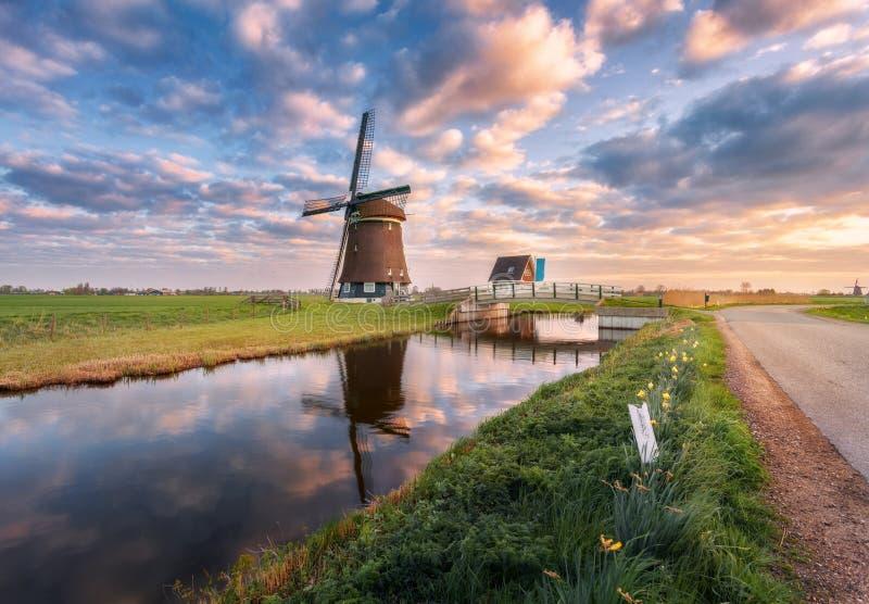 Moulin à vent près du canal de l'eau au lever de soleil aux Pays-Bas images stock