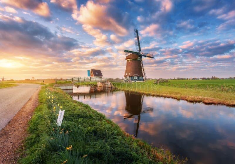 Moulin à vent près du canal de l'eau au lever de soleil aux Pays-Bas photographie stock libre de droits