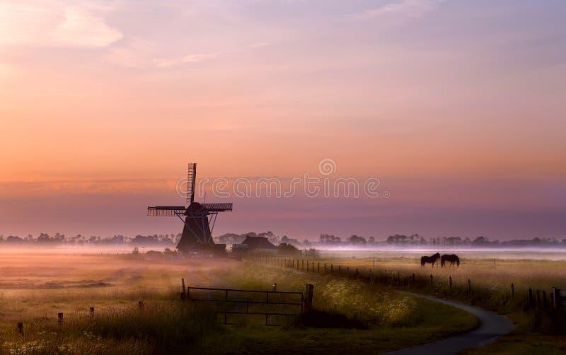 Moulin à vent sur le pâturage au lever de soleil photographie stock