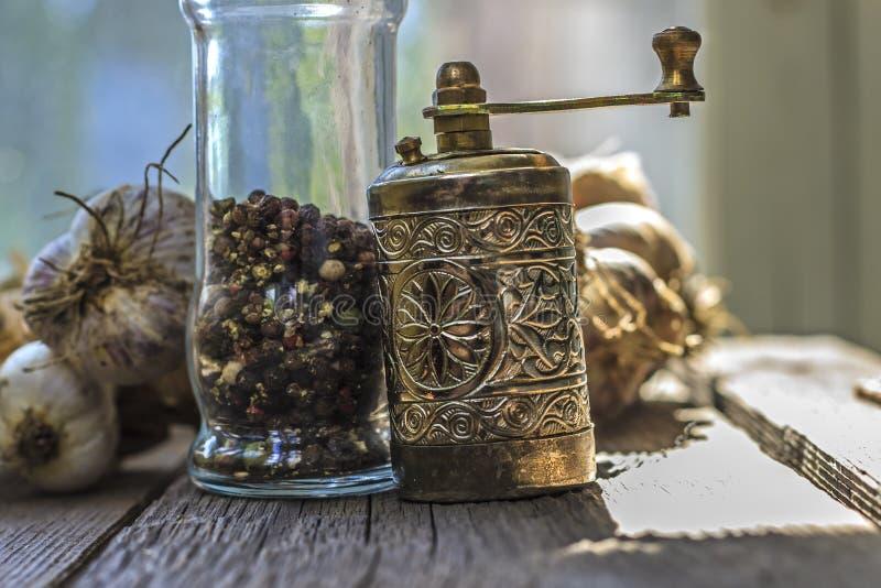 Moulin de poivre d'en cuivre de cru avec un bol en verre pour le poivre photographie stock