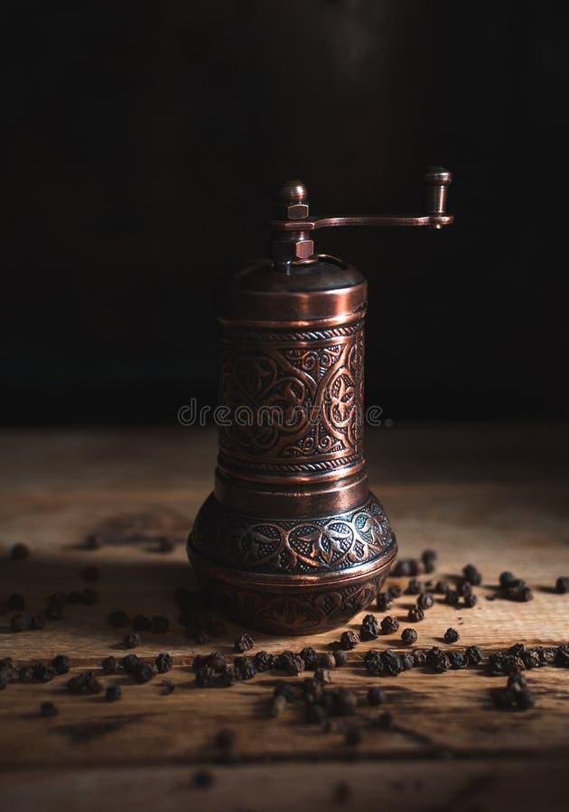 Moulin de poivre d'en cuivre de cru sur le fond en bois image stock