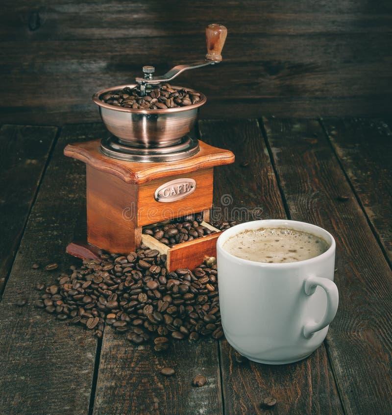 Moulin et tasse à café avec des haricots sur le fond foncé photographie stock