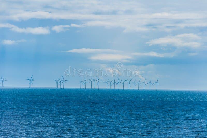 Moulins à vent en mer images stock