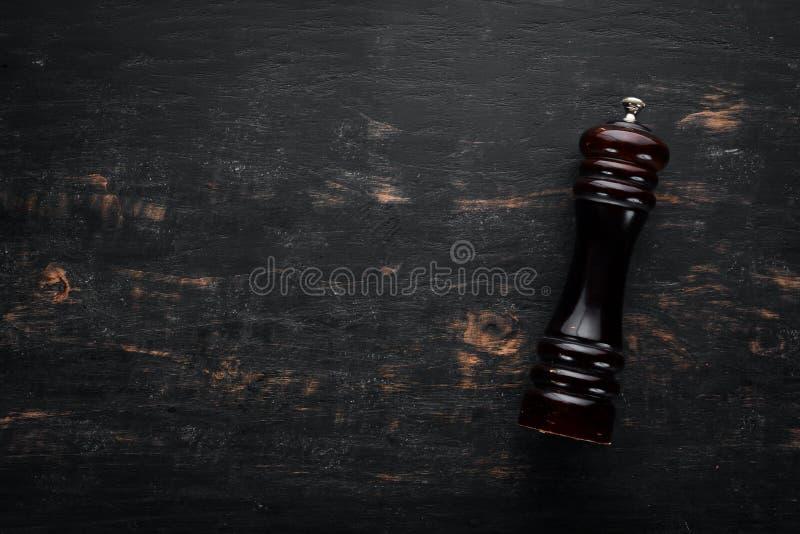 Moulins de poivre en bois Sur un fond en bois noir images stock