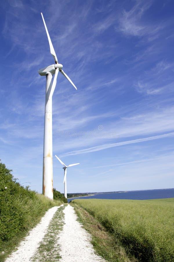 Moulins de vent jumeaux près de la mer photographie stock libre de droits