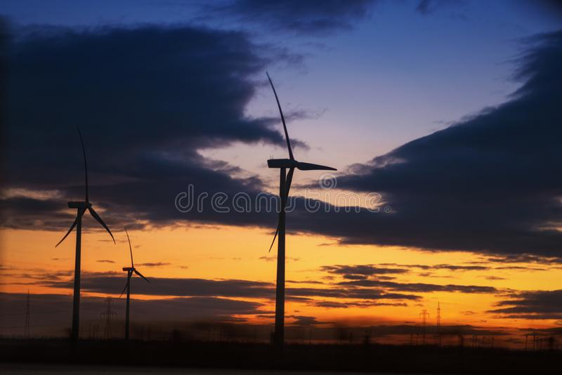 Moulins ? vent au coucher du soleil Turbines de vent dans le domaine vert D?veloppement durable, ?nergie renouvelable Moulins à v image libre de droits