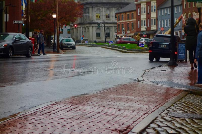Street scene, Portland, Maine, November 2018. Moulton Street with its cobblestones running into Fore Street, and the old United States Custom House Building royalty free stock image