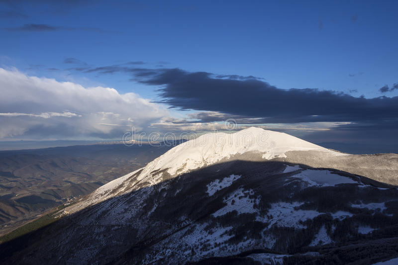 Mount Acuto at sunset in winter, Umbria, Apennines, Italy. Mount Acuto at sunset in winter, blue sky with clods, Umbria, Apennines, Italy royalty free stock photo