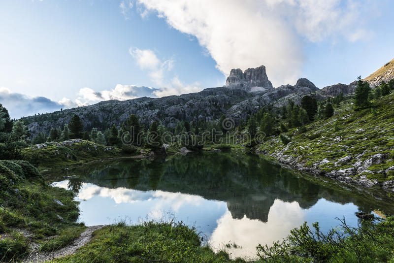 Mount Averau reflected in lake Limedes at sunrise, blue sky with clouds, Dolomites, Veneto, Italy stock photo