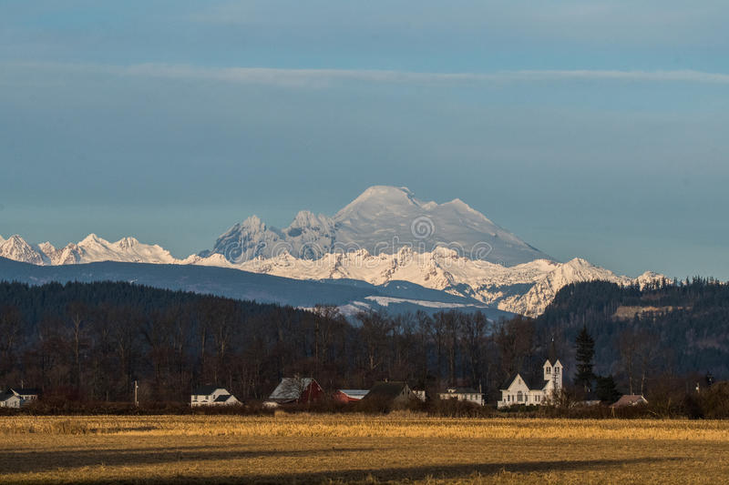 Mount Baker. Viewed across Skagit Valley, WA with Conway church in foreground stock photo