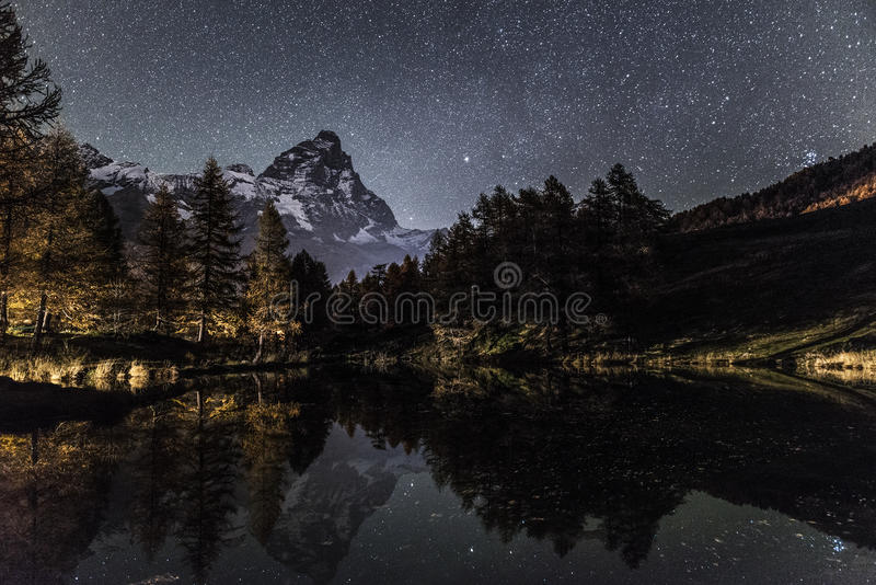 Mount Cervino and Blue Lake in an autumn night. Matterhorn and Blue Lake in an autumn night with starry sky royalty free stock photo