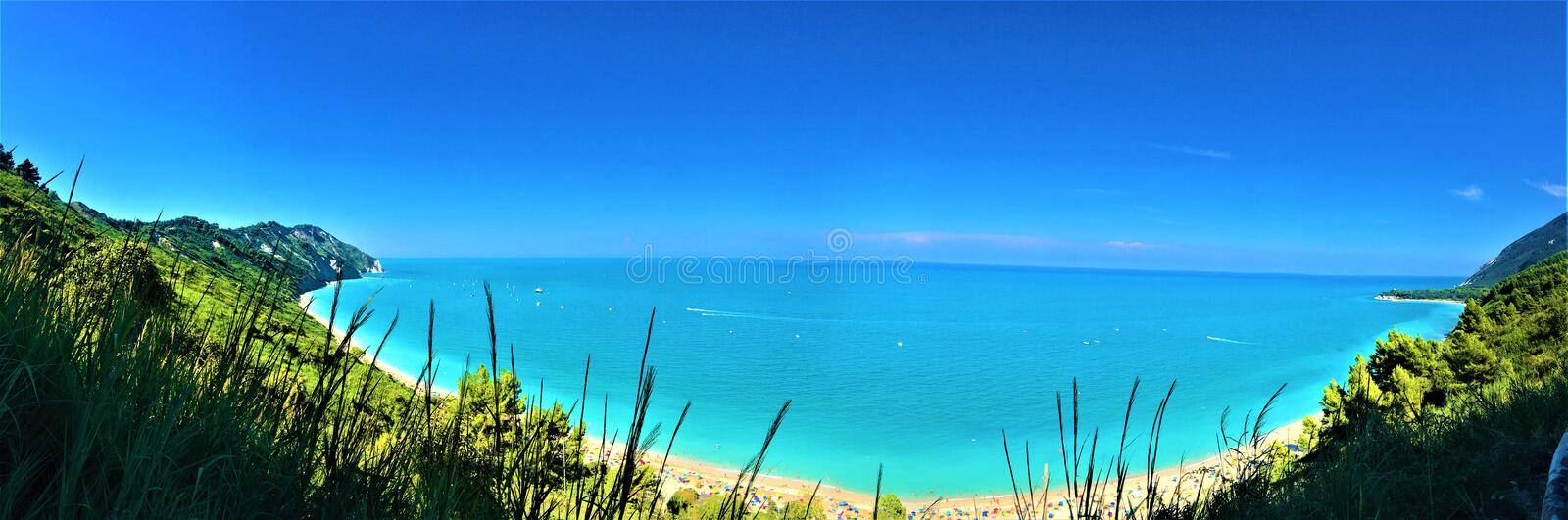 Mount Conero, nature reserve, wild trip. Mount Conesro, Marche, summer vacation, sunny day, blue sky, sane environment, trees, grass, good vibes, limpid water stock photography