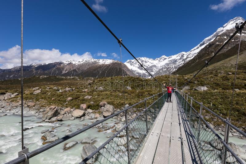 A walker on a suspension bridge on the famous Valley Track in New Zealand`s Mount Cook Aoraki National Park royalty free stock image