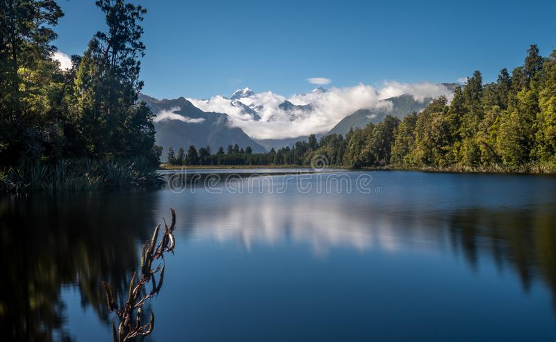 Mount Cook is reflecting in the water of Lake Matheson in New Zealand stock photo