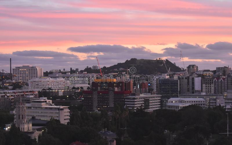 Mount Eden from across Auckland city New Zealand. View of Mount Eden from a tall building in the city of Auckland. With an evening red sky, clouds, after sunset royalty free stock photography