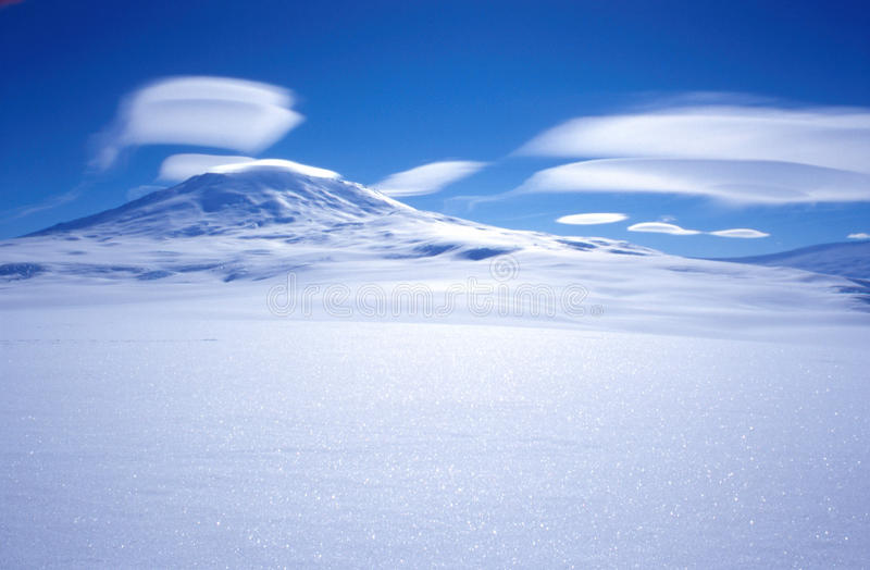 Mount Erebus Clouds. Lenticular clouds over the active volcano Mount Erebus located on Ross Island Antarctica. The USAP station McMurdo is located on Ross Island stock image