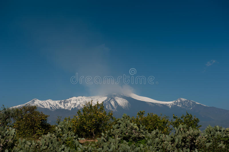 Mount Etna. Big blue copy space ## WS Mount Etna with snow cover and lava flows clearly visible under a big blue clear sky stock photography