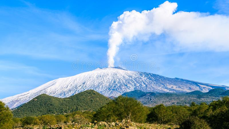 Mount Etna gas emission. Tremor, gases. Snowy Mount Etna after its latest eruption, emitting gases creating a big cloud in the blue sky stock photo