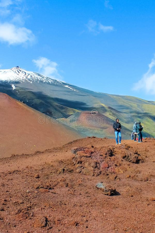 Mount Etna, Sicily, Italy - April 9th 2019: Couple of tourists standing on the Silvestri craters overlooking the very top of Etna royalty free stock images